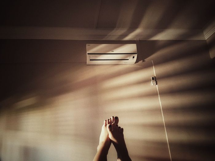 Low section of woman with feet up against air conditioner on wall at home