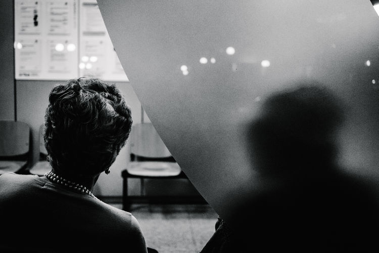 Rear view of woman sitting in waiting room