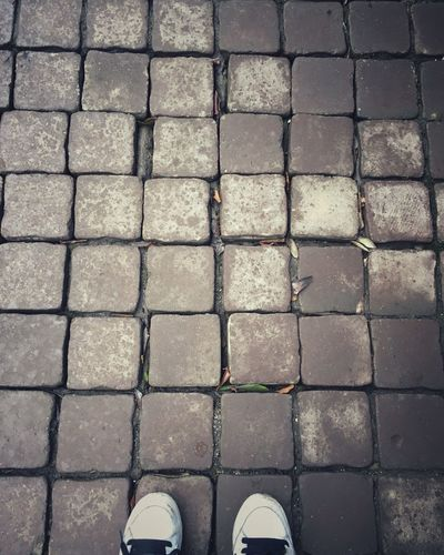 High angle view of shoes on cobblestone footpath