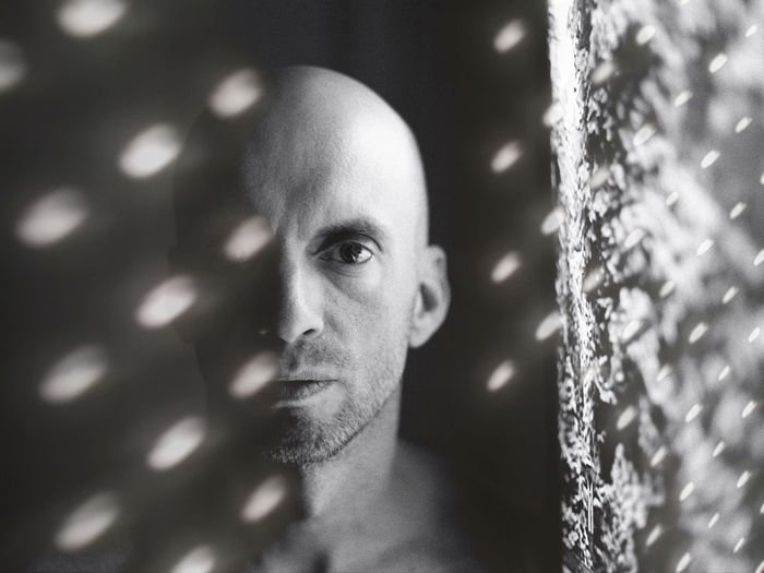 Double Exposure Image Of Bald Man And Lighting Equipment