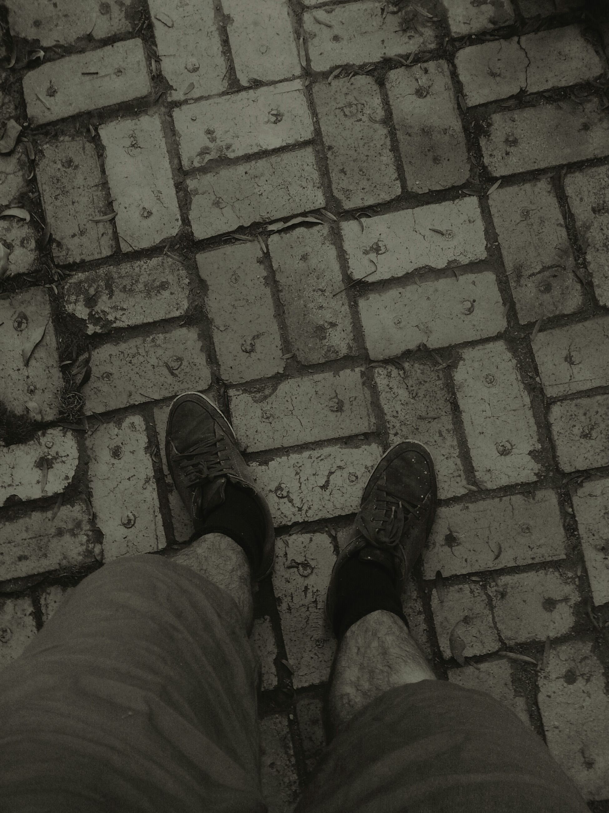 low section, person, shoe, personal perspective, standing, high angle view, lifestyles, human foot, street, men, cobblestone, footwear, leisure activity, directly above, unrecognizable person, footpath, paving stone