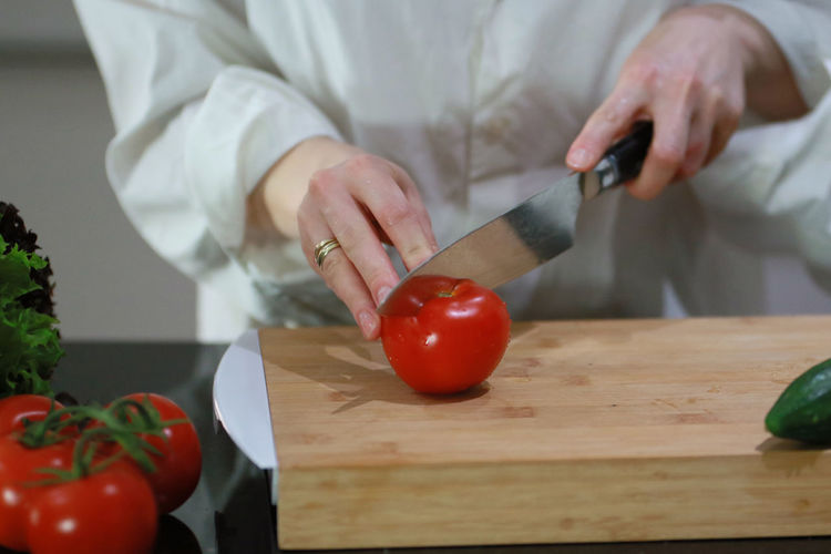 Midsection of man holding red chili peppers on cutting board
