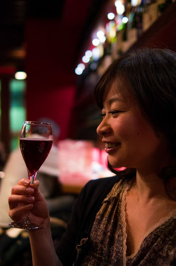 Happy Woman Looking At Wine In Wineglass