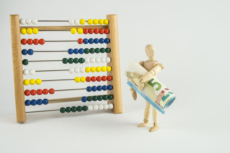 Multi colored abacus calculator and figurine on white background