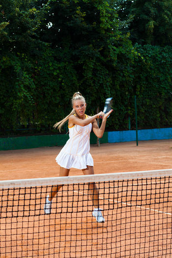 Young woman in a tennis dress returning the ball on a sandy court Women Court One Person Happiness Sport Tennis Smiling Clothing Human Arm Cheerful Arms Raised Racket Adult Young Adult Tennis Racket Limb Emotion Playing Full Length Human Limb Skill  Outdoors