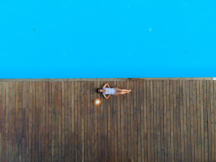 Woman sitting on wood against blue color of the swimming pool