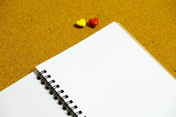 High angle view of blank spiral notebook on table