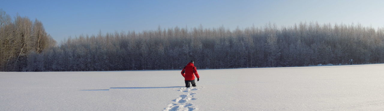 Person walking on snow covered field