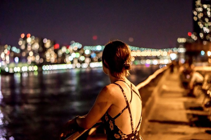Rear view of woman leaning on promenade railing by river at night