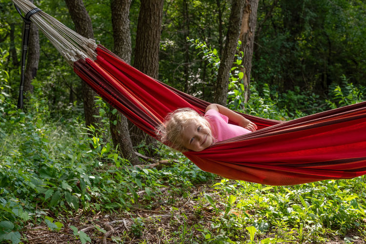 Rear view of woman sitting on hammock in forest
