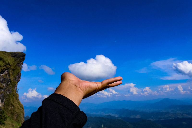 Midsection of person holding mountain against blue sky
