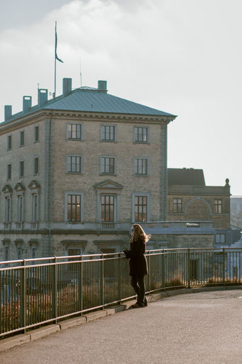Rear view of woman walking on building in city against sky