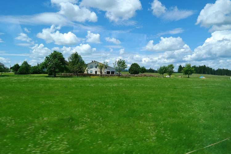 View of house on grassy landscape against cloudy sky