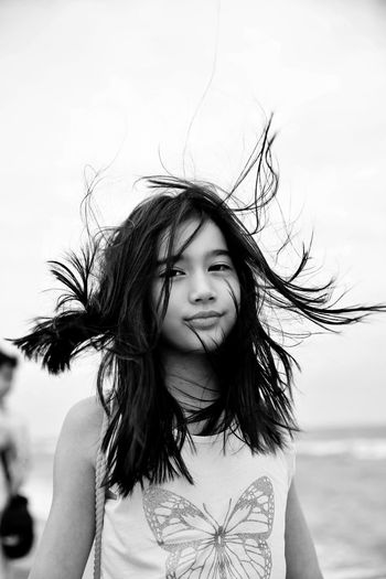 Girl holding hair and standing at shore
