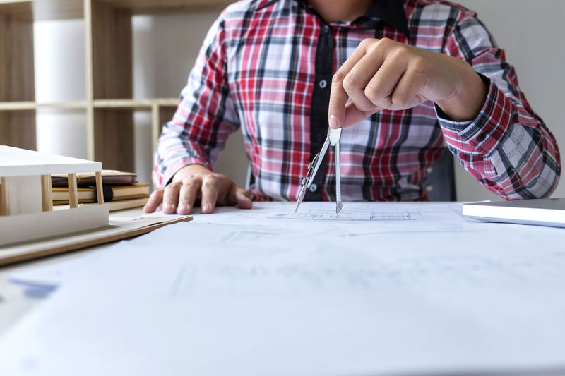 Midsection of architect using drawing compass while working at desk in office