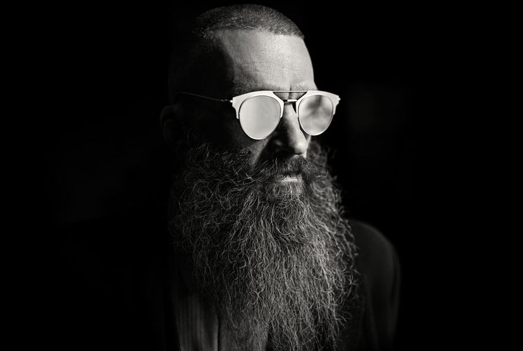 Rear view of man wearing sunglasses against black background