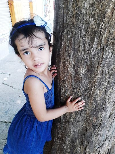 Portrait of cute girl standing by tree trunk