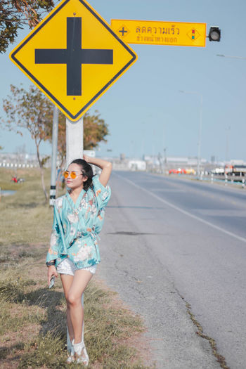 Full length of woman standing on road by sign