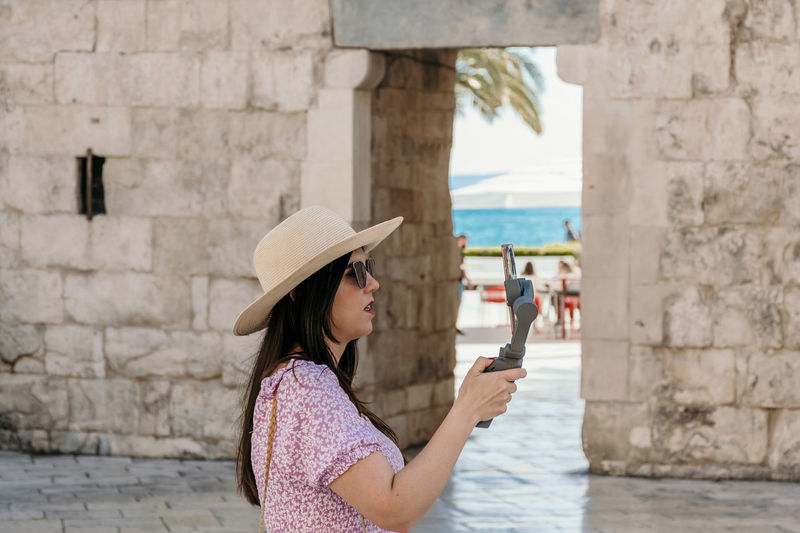 Side view of woman using mobile phone against brick wall