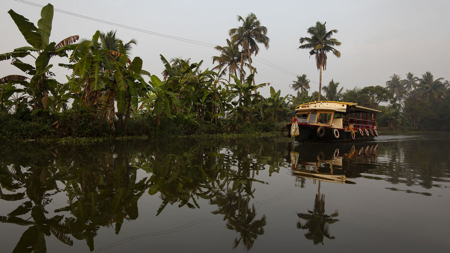 Tourist boat plying their trade on the Meenakshi River Reflection Plant Tree Water Waterfront Nature Transportation Sky Lake Palm Tree Tropical Climate Day No People Growth Tranquility Outdoors Tourist Boat