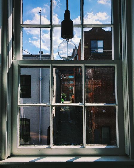 Light bulb hanging against glass window