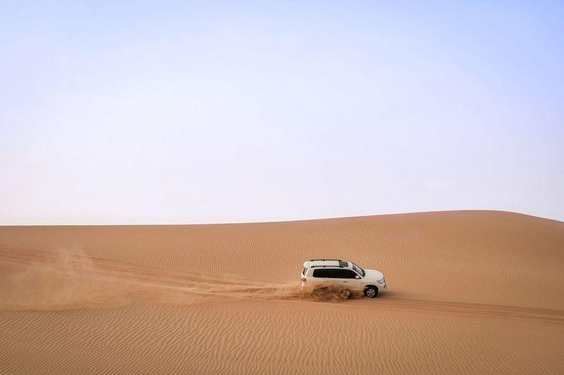 Car on desert land against sky
