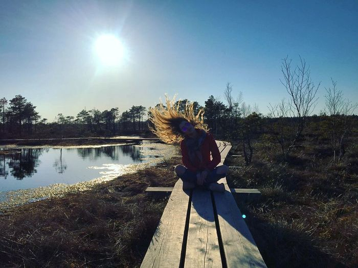 Woman standing by lake against clear sky
