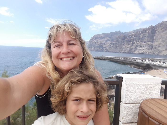 Portrait of happy mother with son standing against sea