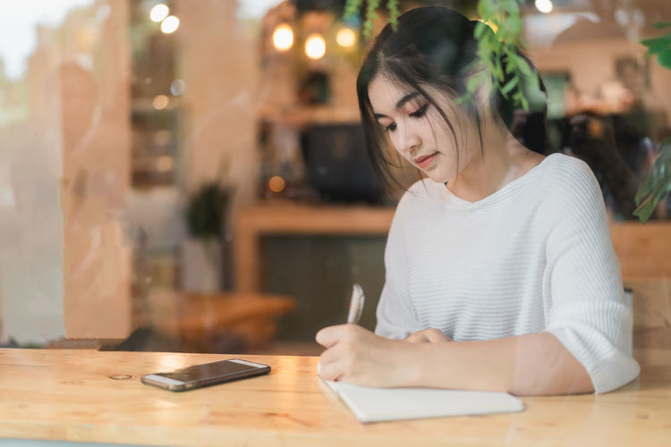Young woman using mobile phone while sitting on table