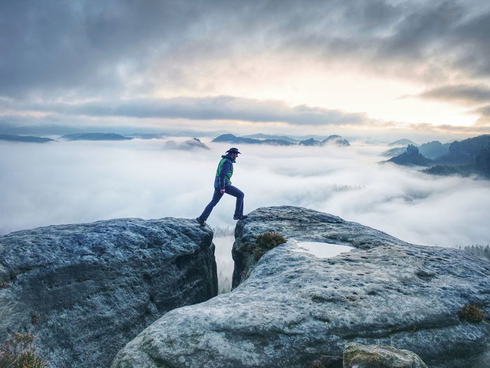 Male hiker finnaly standing on a rock stock and enjoying foggy mountain view