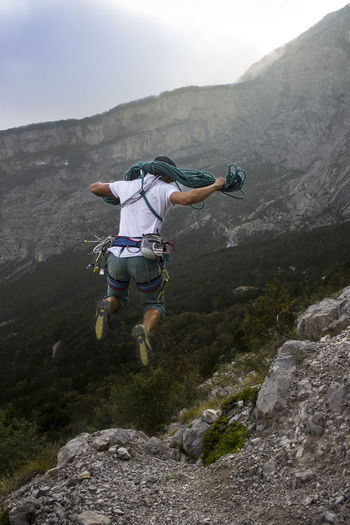 Rear view of man jumping on mountain against sky