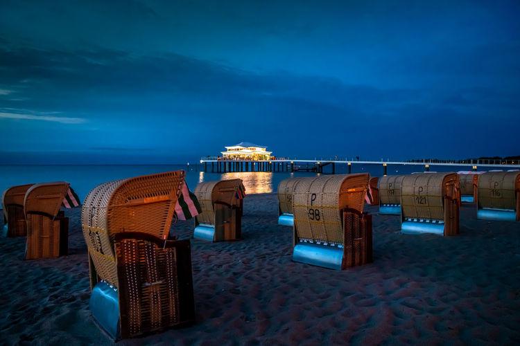 Hooded chairs on beach against sky at dusk