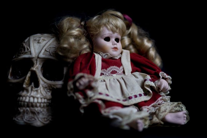 Close-Up Of Doll And Skull Against Black Background