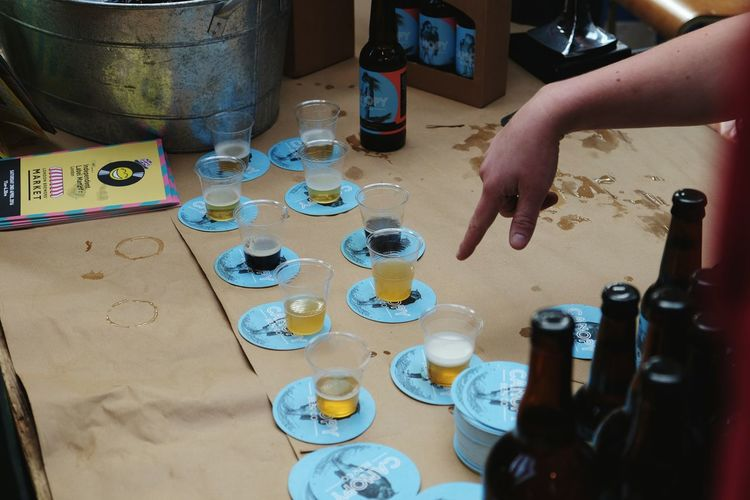 Cropped image of person pointing on beer glasses on table
