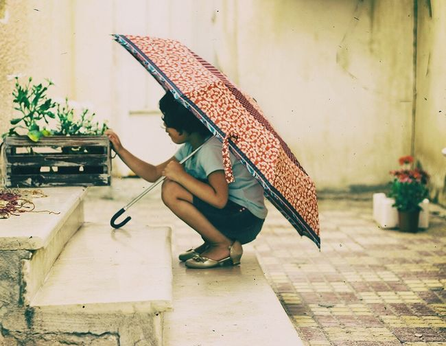 Side view of a girl holding umbrella on footpath