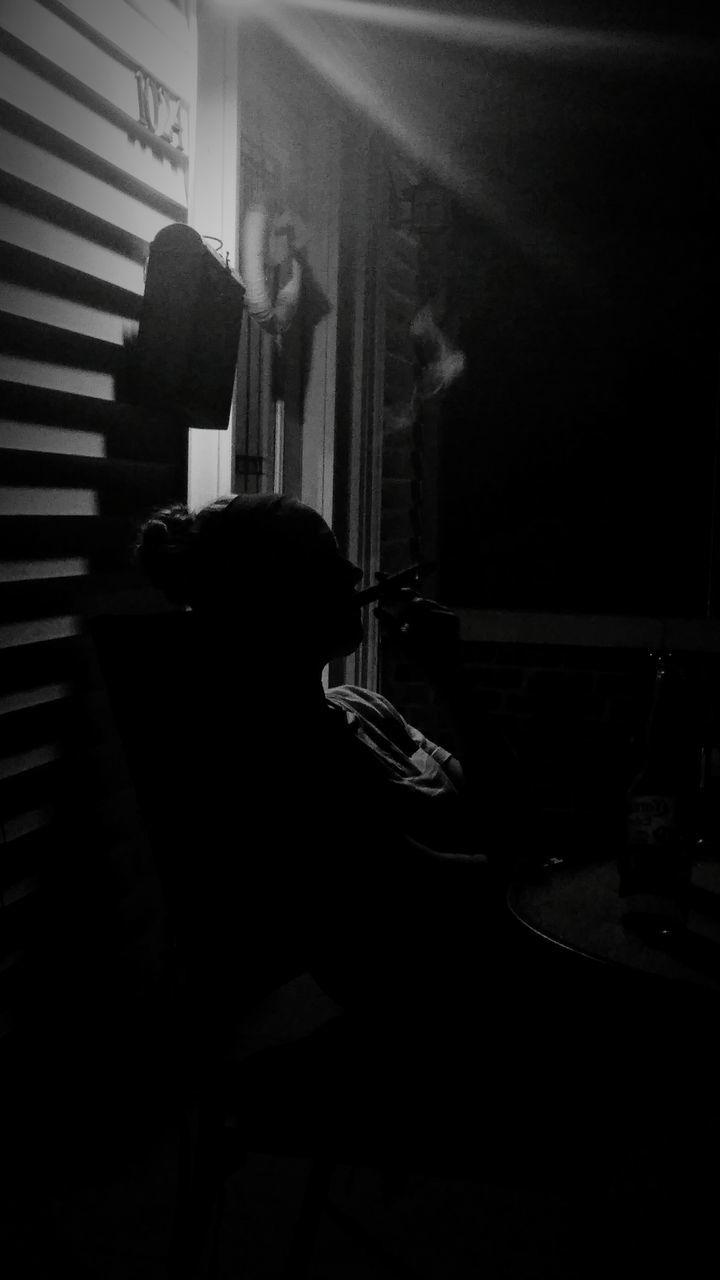 Silhouette of woman smoking cigar