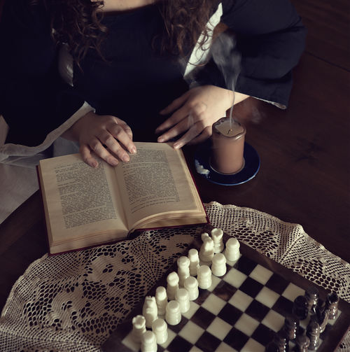 Midsection of woman with book at table
