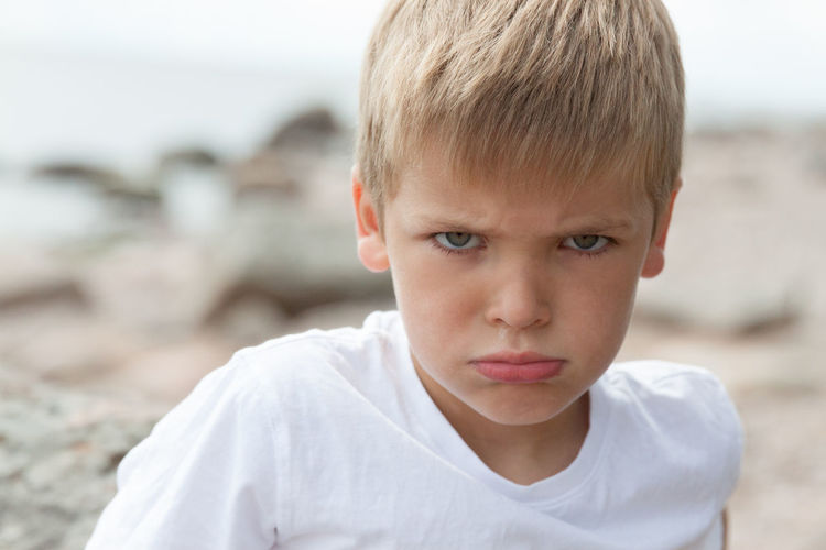 Angry looking boy at the Baltic sea coast Angry Boy Blond Hair Boys Child Childhood Children Only Close-up Day Disappointment Eye Color Face Expression Focus On Foreground Front View Green Eyes Happy Headshot Human Body Part Looking At Camera Males  One Boy Only One Person Outdoors People Portrait Pretty