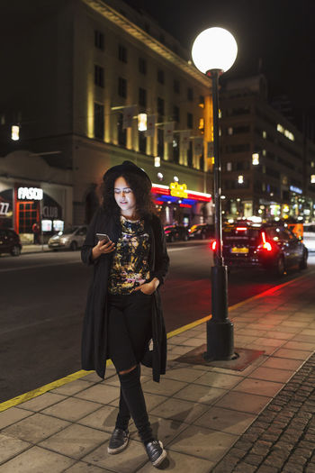 Full length of woman standing on city street at night