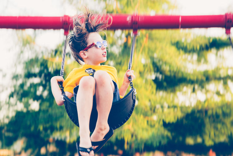 Low angle view of boy wearing sunglasses swinging outdoors