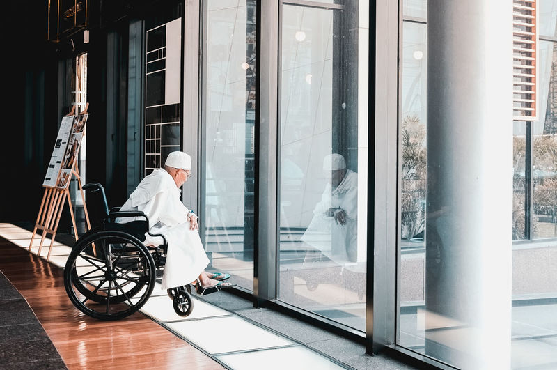 Man sitting on wheelchair in corridor