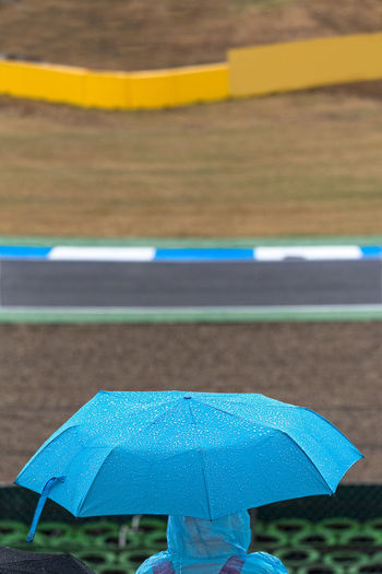 A motorsport spectator shelters from the rain under a blue umbrella and poncho in the grandstands between races. Blue Circuit Cover Covered Entertainment Fans View Motorsport Protection Racing Racing Car Raining Sheltering Sport Venue Tire Wall Track Track Curb Track Side Umbrella Waiting Waterproofs Wet Road Security Day Focus On Foreground Water Nature Rain Transportation Outdoors Safety No People Rainy Season Road Marking Marking