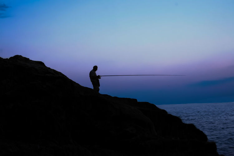 Silhouette Man Fishing On Rock Against Clear Sky At Dusk