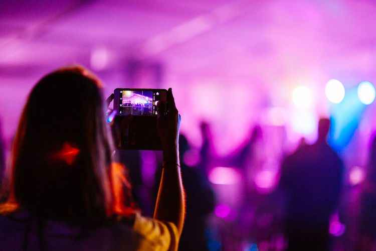 Rear View Of Woman Photographing In Popular Music Concert At Nightclub