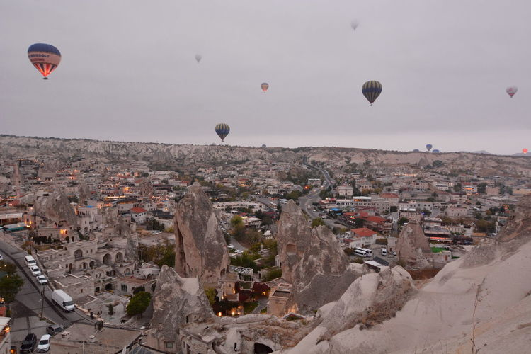 Hot air balloons flying over buildings in city