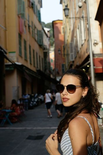 Portrait of young woman wearing sunglasses in city