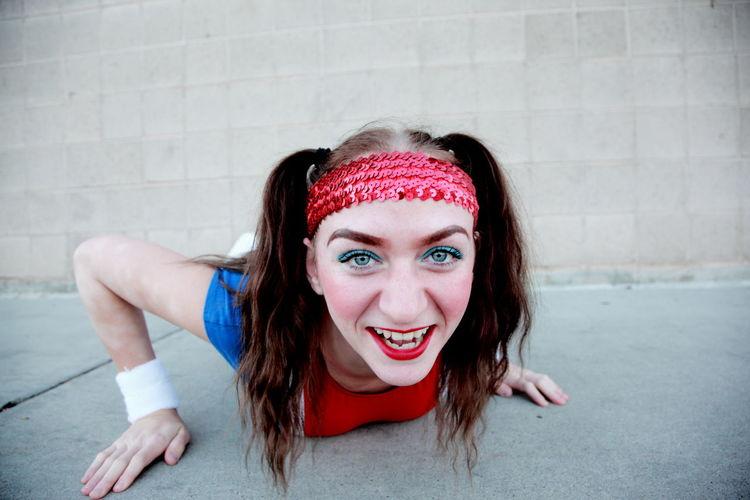 Portrait of cheerful teenage girl lying on street