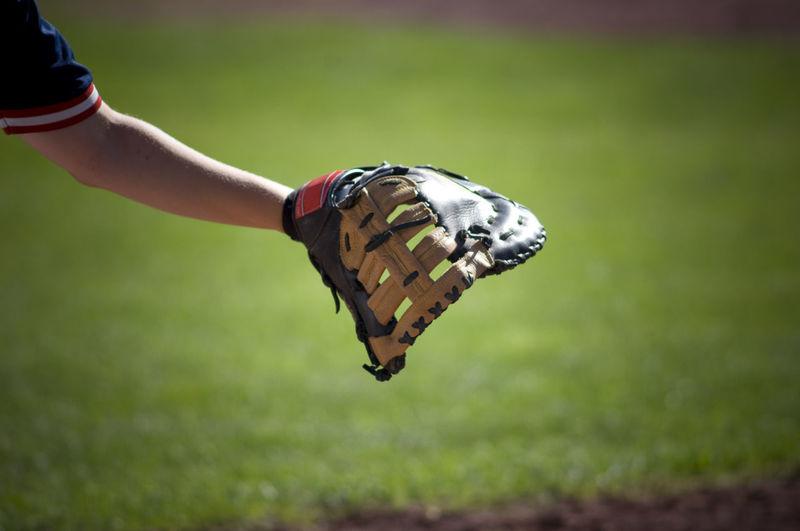 Close-up of hand holding umbrella on field
