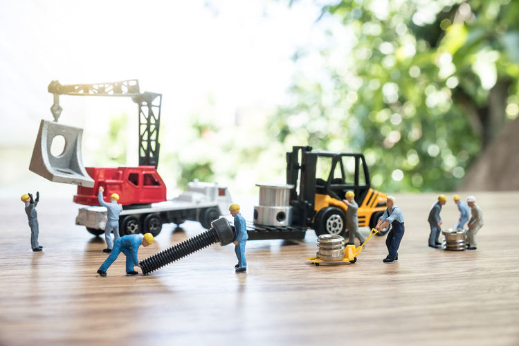 Close-up of figurines with toy crane and forklift with equipment on table