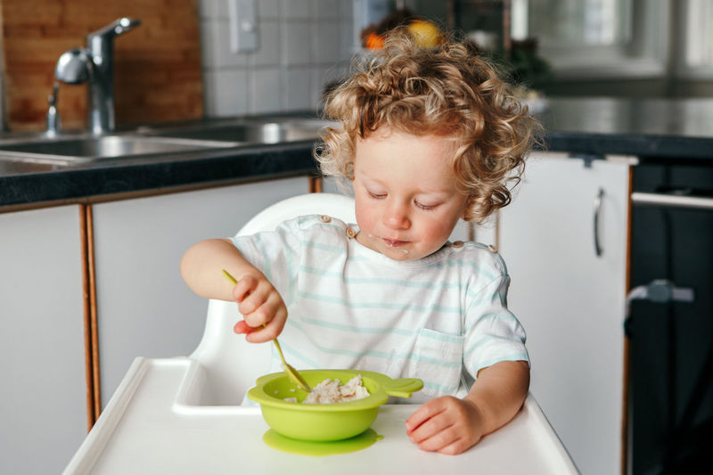 Caucasian curly kid boy sitting in high chair eating cereal puree with spoon. healthy eating